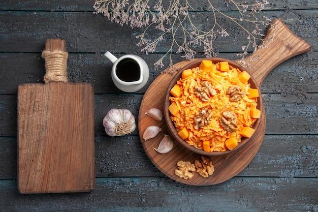 Widok z góry świeża sałatka z marchwi z czosnkiem i orzechami włoskimi na ciemnoniebieskim biurku z orzechami w kolorze zdrowej sałatki