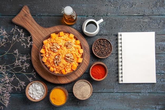Widok z góry świeża sałatka z marchwi z orzechami włoskimi i przyprawami na ciemnym biurku orzechowa dieta kolorowa sałatka zdrowotna