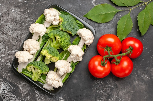 Widok z góry świeże brokuły i kalafior na czarnej prostokątnej płycie pomidorów na ciemnej powierzchni