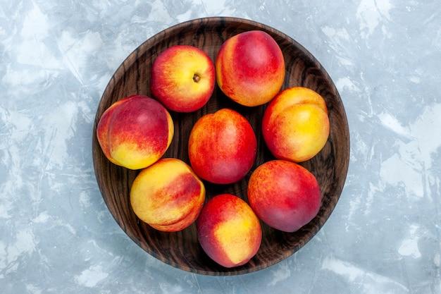Widok z góry świeże brzoskwinie łagodne i smaczne owoce wewnątrz brązowego talerza na jasnobiałym biurku