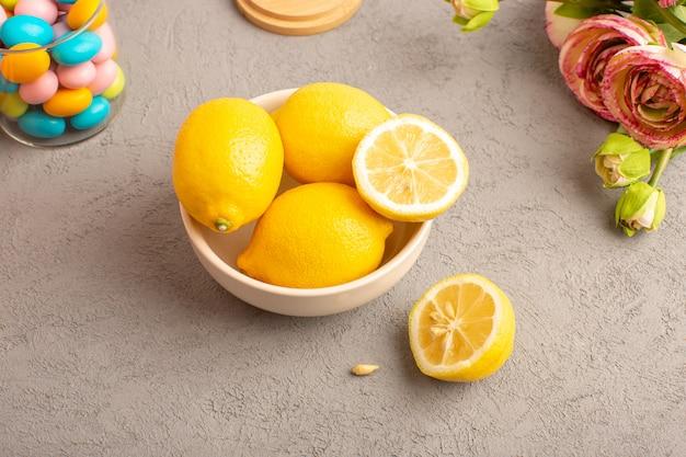 Widok z góry świeże cytryny kwaśne dojrzałe w całości z kolorowymi cukierkami suszone kwiaty łagodny cytrus tropikalny tropikalny witaminowy żółty na kremowym biurku