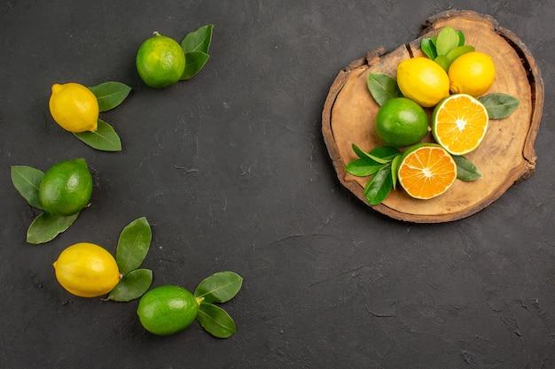 Widok z góry świeże cytryny kwaśne na ciemnych owocach cytrusowych limonki