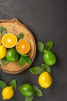 Widok z góry świeże cytryny kwaśne na ciemnych owocach stołowych limonka cytrusowa