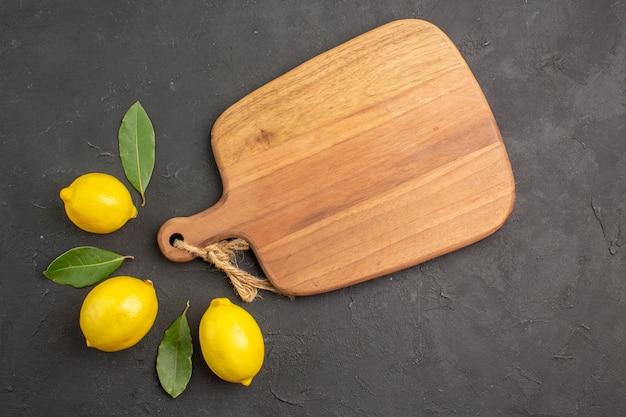 Widok z góry świeże cytryny kwaśne wyłożone ciemnymi owocami stołowymi limonkowo-żółtymi cytrusami