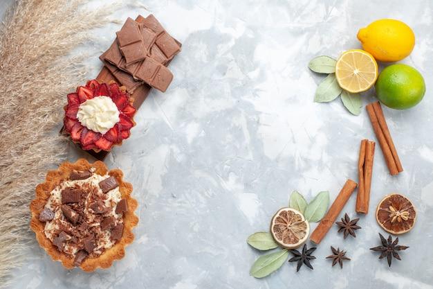 Widok z góry świeże cytryny soczyste i kwaśne z cynamonem i ciastami na białym biurku tropikalne egzotyczne owoce cytrusowe