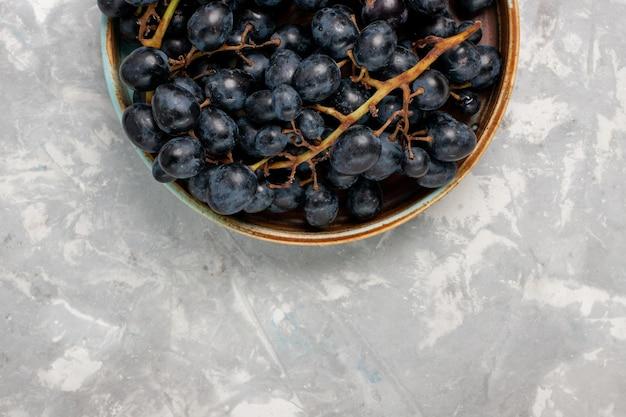 Widok z góry świeże czarne winogrona soczyste aksamitne słodkie owoce na jasnobiałym biurku