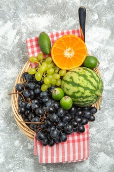 Widok z góry świeże czarne winogrona z pomarańczą i feijoa na białej powierzchni owoce aksamitne dojrzałe świeże
