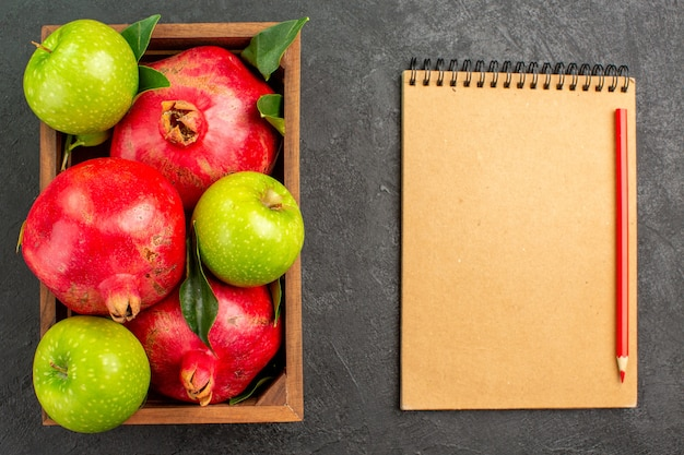 Widok z góry świeże czerwone granaty z zielonymi jabłkami na ciemnym biurku kolor dojrzałych owoców