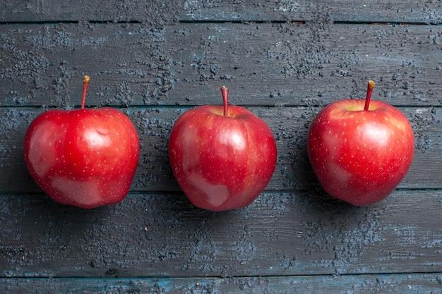Widok z góry świeże czerwone jabłka dojrzałe i aksamitne owoce wyłożone na ciemnoniebieskiej podłodze wiele owoców czerwonych świeżych roślin kolor drzewa