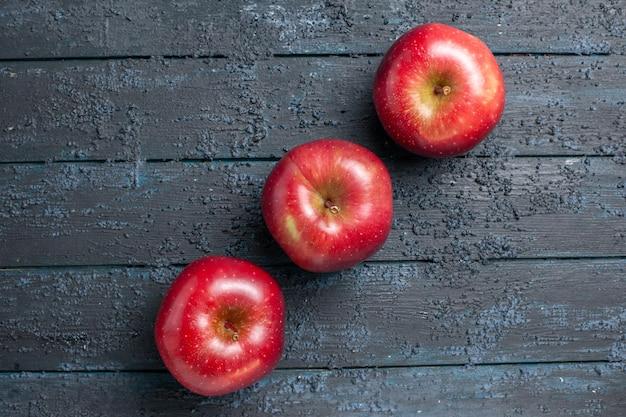 Widok z góry świeże czerwone jabłka dojrzałe i aksamitne owoce wyłożone na ciemnoniebieskim biurku wiele owoców czerwonych świeżych roślin kolor drzewa