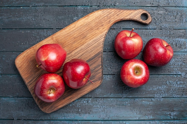 Widok z góry świeże czerwone jabłka łagodne dojrzałe owoce na ciemnoniebieskim biurku kolor owoców czerwona roślina witamina świeża