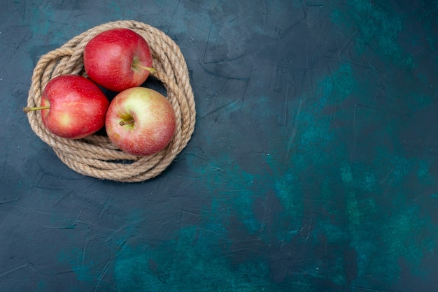 Widok z góry świeże czerwone jabłka soczyste i łagodne na ciemnoniebieskim tle dojrzałe owoce świeża witamina