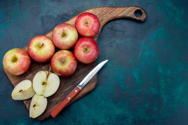Widok z góry świeże czerwone jabłka soczyste i łagodne z brązowym biurkiem na ciemnoniebieskim tle owoce świeże dojrzałe łagodne witamina