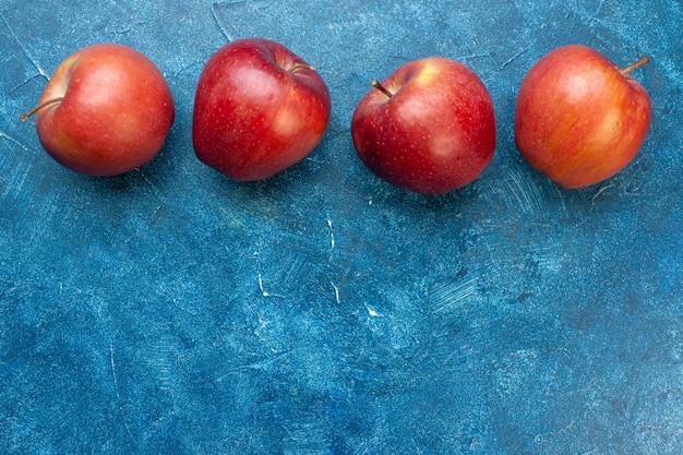 Widok z góry świeże czerwone jabłka wyłożone na niebieskim stole