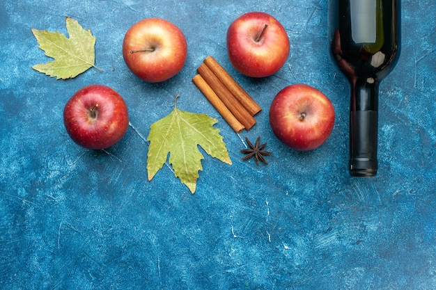 Widok z góry świeże czerwone jabłka z butelką wina na niebieskim biurku dojrzałe owoce alkohol kolor drzewo zdjęcia