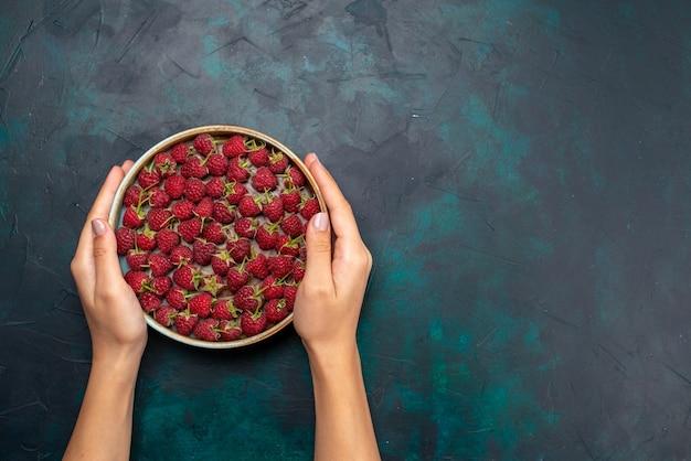 Widok z góry świeże czerwone maliny kwaśne i łagodne jagody na ciemnym biurku owoce łagodne świeża witamina