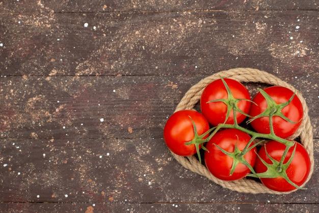 Widok z góry świeże czerwone pomidory dojrzałe i całe na drewnianym brązu