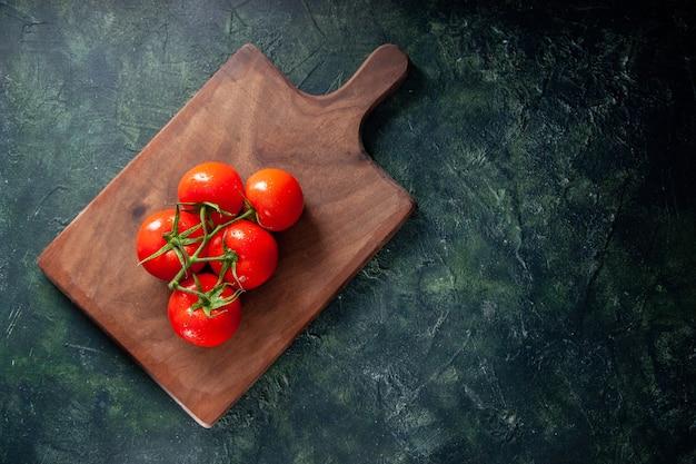 Widok z góry świeże czerwone pomidory na desce do krojenia ciemne tło jedzenie obiad dojrzałe dieta posiłek kolor sałatka zdrowie