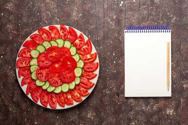 Widok z góry świeże czerwone pomidory pokrojone świeże sałatki na brązowym biurku