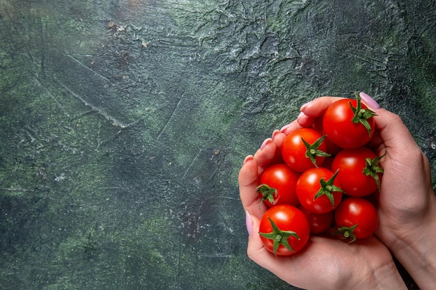Widok z góry świeże czerwone pomidory w rękach kobiet na ciemnej powierzchni
