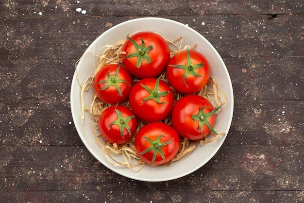 Widok z góry świeże czerwone pomidory wewnątrz białej płyty na drewnianym brązowym