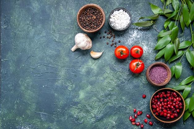 Widok z góry świeże czerwone pomidory z czosnkiem i przyprawami na ciemnym tle kolor dojrzała sałatka posiłek zdjęcie dieta zdrowotna