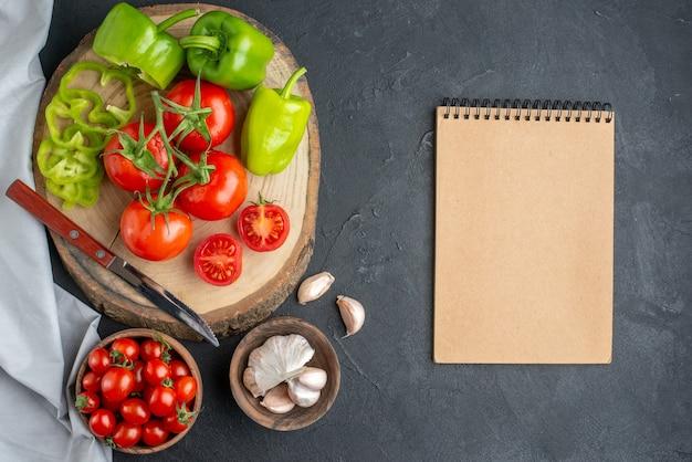 Widok z góry świeże czerwone pomidory z czosnkiem i zieloną papryką na ciemnej powierzchni