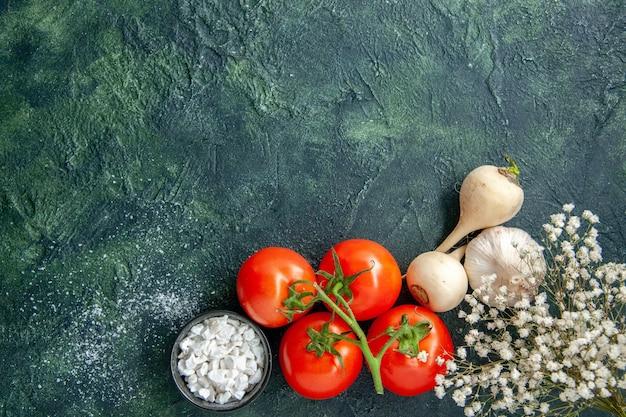 Widok z góry świeże czerwone pomidory z czosnkiem na ciemnym tle dieta zdrowotna sałatka posiłek jedzenie kolor zdjęcie