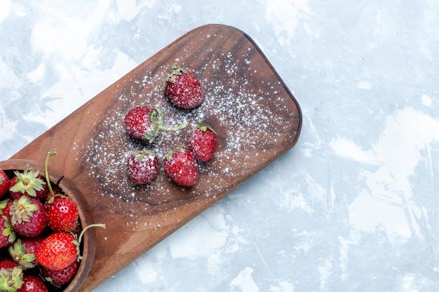 Widok z góry świeże czerwone truskawki aksamitne jagody na jasnym biurku