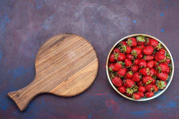 Widok z góry świeże czerwone truskawki łagodne owoce jagody na ciemnoniebieskim biurku jagody owoce łagodne letnie jedzenie witamina dojrzałe