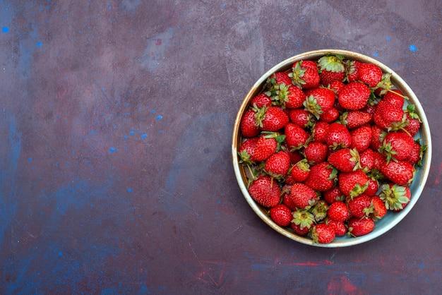Widok z góry świeże czerwone truskawki łagodne owoce jagody na ciemnoniebieskim tle owoce jagodowe łagodne letnie jedzenie witamina dojrzałe