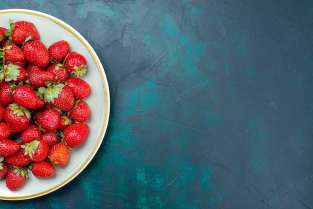 Widok z góry świeże czerwone truskawki łagodne owoce jagody wewnątrz płyty na ciemnoniebieskim tle owoce jagodowe łagodne lato
