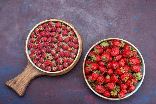 Widok z góry świeże czerwone truskawki łagodne owoce z malinami na ciemnoniebieskiej powierzchni owoce jagodowe łagodne letnie jedzenie