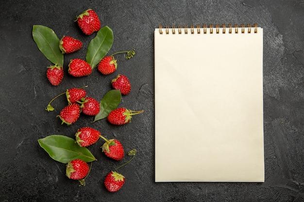 Widok z góry świeże czerwone truskawki na ciemnym stole owoce jagodowe dojrzały kolor