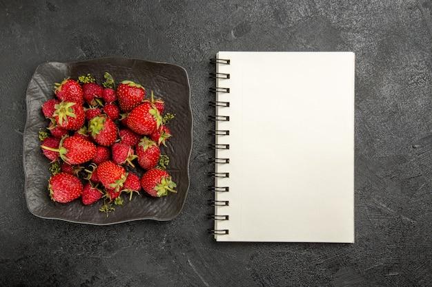 Widok z góry świeże czerwone truskawki wewnątrz płyty na ciemnym stole owoce jagodowe