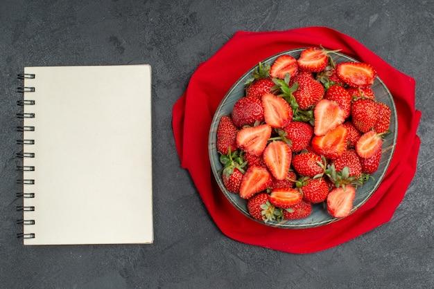Widok z góry świeże czerwone truskawki wewnątrz talerza z notatnikiem na ciemnym tle