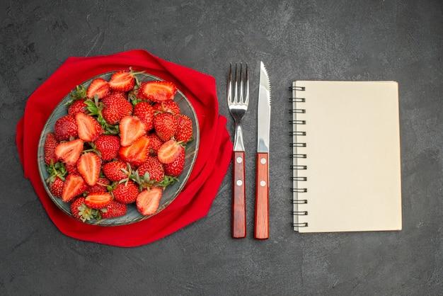 Widok z góry świeże czerwone truskawki wewnątrz talerza ze sztućcami na ciemnym tle