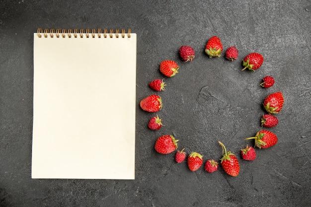 Widok z góry świeże czerwone truskawki wyłożone ciemnoszarymi owocami jagodowymi w kolorze stołu