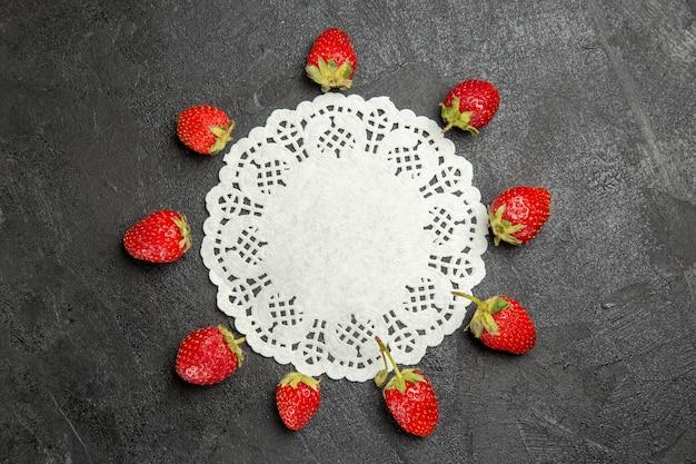 Widok z góry świeże czerwone truskawki wyłożone ciemnymi owocami jagodowymi koloru stołu