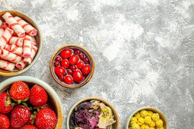 Widok z góry świeże czerwone truskawki z cukierkami na białej podłodze owocowe słodkie cukierki kolor