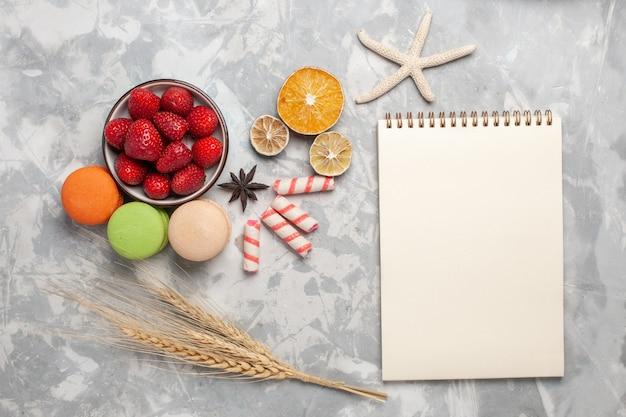 Widok z góry świeże czerwone truskawki z francuskimi makaronikami na jasnobiałym biurku ciasto owocowe herbatniki słodki cukier