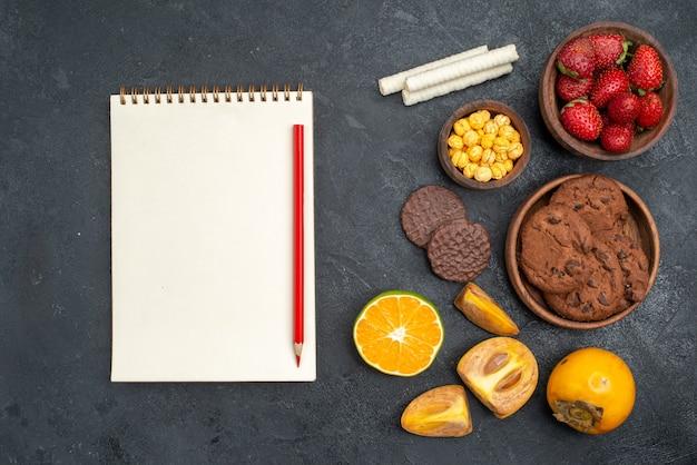 Widok z góry świeże czerwone truskawki z herbatnikami na ciemnym stole słodkie ciasteczko cukrowe