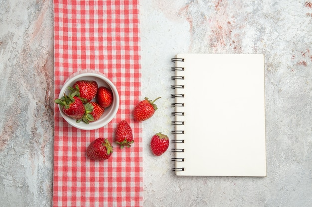 Widok z góry świeże czerwone truskawki z notatnikiem na białym stole owoce jagodowe czerwone świeże
