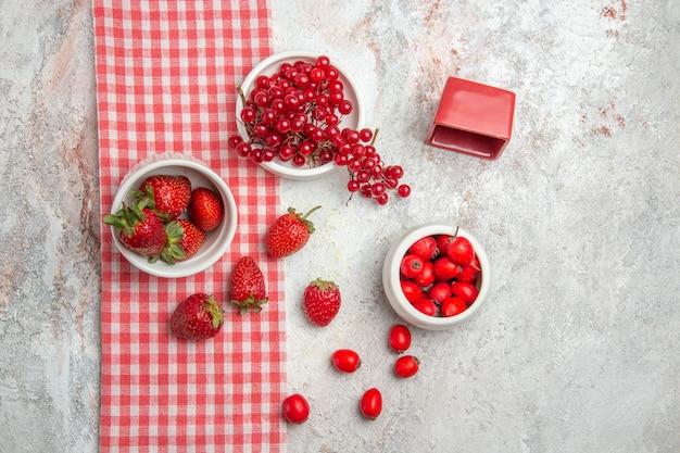 Widok z góry świeże czerwone truskawki z owocami na białym stole owoce jagodowe czerwone świeże
