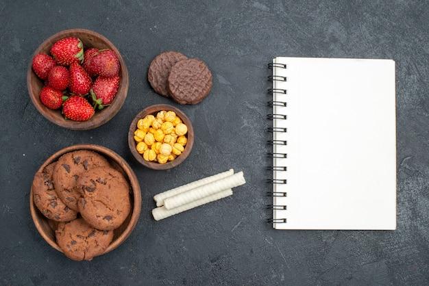 Widok z góry świeże czerwone truskawki ze słodkimi ciasteczkami na ciemnym stole cukru ciasteczka