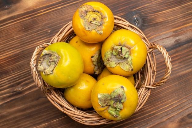 Widok z góry świeże dojrzałe persimmon dojrzałe słodkie owoce na brązowym stole owoce mellow dojrzałe