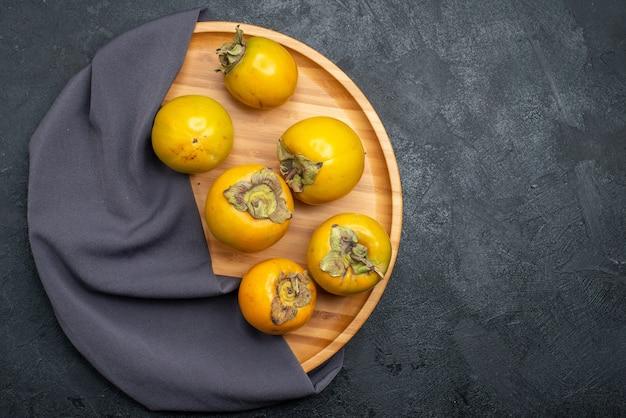 Widok z góry świeże dojrzałe persimmon dojrzałe słodkie owoce na ciemnym stole owoce łagodne dojrzałe
