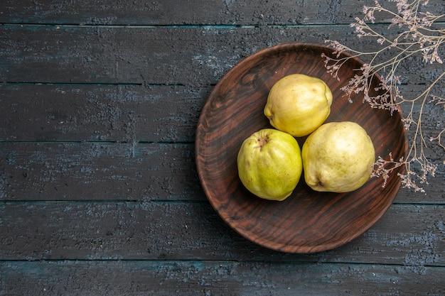 Widok z góry świeże dojrzałe pigwy kwaśne owoce wewnątrz talerza na ciemnoniebieskim rustykalnym biurku roślina owoce dojrzałe świeże drzewo