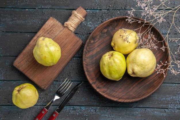 Widok z góry świeże dojrzałe pigwy kwaśne owoce wewnątrz talerza na ciemnoniebieskim rustykalnym biurku świeża roślina dojrzałe owoce drzewa