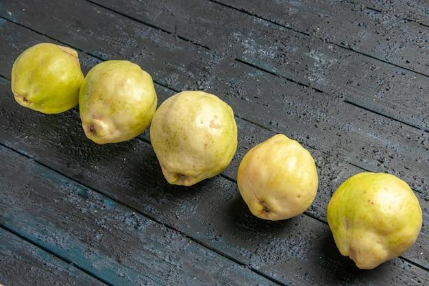Widok z góry świeże dojrzałe pigwy kwaśne owoce wyłożone na ciemnoniebieskim rustykalnym biurku roślina drzewo owocowe dojrzałe świeże